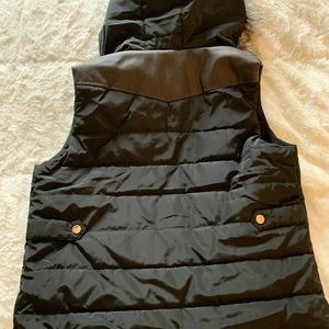 Black vest with brown detail and red buffalo plaid